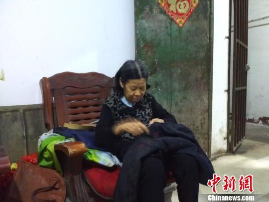 李新彩老人给张满英缝补衣服。 谢丽萍 摄